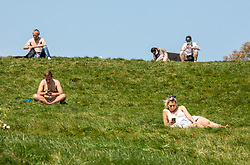 © Licensed to London News Pictures. 23/04/2020. London, UK. Londoners go out to Primrose Hill in the sunshine during lockdown as temperatures reach 24c as queues are seen outside popular food takeaway restaurants and an increase in traffic on the roads as ministers grapple with when and how to release people from the coronavirus pandemic lockdown. Photo credit: Alex Lentati/LNP