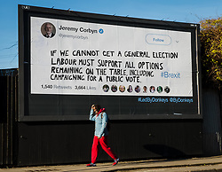 """© Licensed to London News Pictures. 14/02/2019. London, UK.  A man walks past a new Jeremy Corbyn billboard from """"Led By Donkeys"""" that has been put up in Mr Corbyn's Islington constituency with a message asking for Labour party support on a pubic vote on Brexit. A previous billboard, errected in the same place on Monday was reportedly removed by Islington Council, who later replaced the blank board when challenged. Photo credit: Vickie Flores/LNP"""