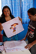 Amanda holds up one of the tea towels that has been painted by one of the mothers at the community library, Biblioteca Comunitaria do Arquipelago, Porte Alegre, Brazil. <br /> <br /> Cirandar is working in partnership with  C&A and C&A Instituto to implement a network of Community Libraries in eight communities of Porto Alegre.