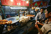 Food stall for the Indian / Chinese fast food dishes in the town square in Ujjain, India. Three dishes are written on the red board above - Gobi Manchurian (gobi=cauliflower), veg noodles and paneer (cottage cheese) chilli. What is currently being prepared on this mobile food cart is 'pav bhaji' Pav literally means 'bun-bread', which is what is seen on the big iron plate on the left side. 'Bhaji' is a mixture of a few different vegetables - onions, potatoes, tomatoes, cauliflower, cabbage, eggplant, carrots, peas, etc.. Lying in the middle of the two iron plates, are bread base for pizzas. (Supporting image from the project Hungry Planet: What the World Eats)
