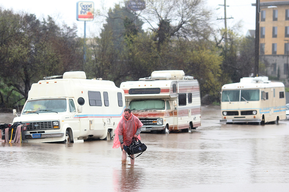 A man who lives in his RV, which was parked in the 300 block of Griffith Street in Salinas, California walks through the flooded street on Feb. 20, 2017.