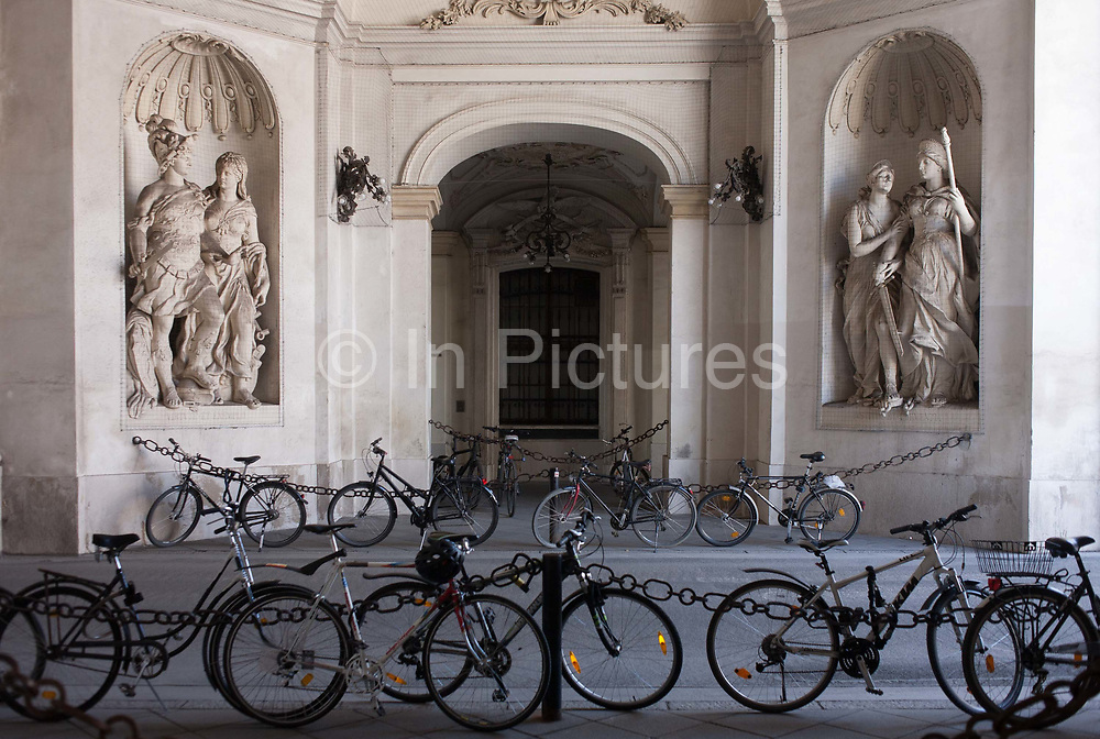 Bikes are locked up on railings beneath Romanesque figures in the Hofburg Kaiserappartements, on 28th June 2016 in Vienna, Austria. Hofburg Palace is the former imperial palace forming part of the official residence and workplace of the President of Austria. Built in the 13th century and expanded in the centuries since, the palace has housed some of the most powerful people in European and Austrian history, including monarchs of the Habsburg dynasty, rulers of the Austro-Hungarian Empire.