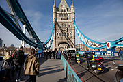 Various modes of transport crossing Tower Bridge, London. Pedestrians and motorosts alike ross this iconic building