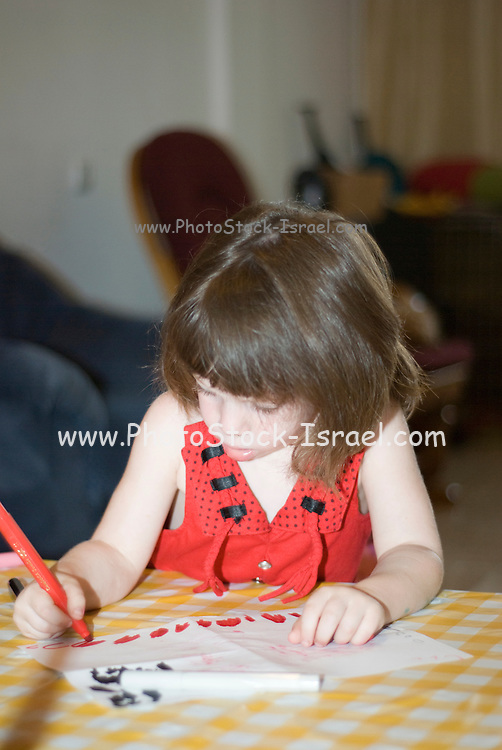girl aged 3 drawing on paper with crayons Model Release Avalable
