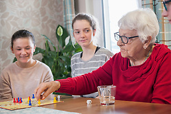 Girls playing ludo board game with senior women in rest home