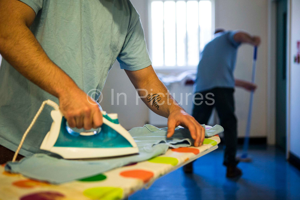 A prisoner ironing his t-shirt the the corridor ready for a family visit, he has 'Nan' tattooed on his arm. Beaufort House, a skill development unit for enhanced prisoners. Part of HMP/YOI Portland, a resettlement prison with a capacity for 530 prisoners. Dorset, United Kingdom.