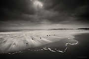 Nominated for 11th International B&W Spider Awards<br /> <br /> Shot on Llanddwyn beach as everyone else was leaving - well it was a bitter cold evening, no sunset, no 'obvious' excitement, but I was utterly connected that evening. In the darkness and solitude I became one with the peace, the dusk, the gentleset lapping sounds at the shore, the occassional oystercatcher calling as it skimmed the sea. I photographed gentle events...© Glyn Davies 2012  All rights reserved. No copying or use on any website is either permitted or implied. Action WILL be taken against infringers.