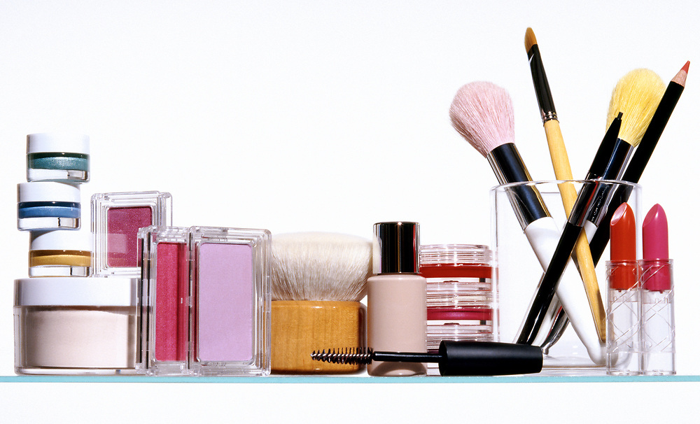 Row of various generic makeup and cosmetic application products on a glass shelf