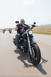 Roadside Marty riding north on highway 79 on the Run to the Line for lunch and biker vs Cowboy rodeo games at the Spur Creek Ranch in Newell during the annual Sturgis Black Hills Motorcycle Rally. SD, USA. Wednesday August 9, 2017. Photography ©2017 Michael Lichter.