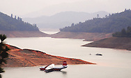 A firefighting plane is moored in a drought-stricken Lake Shasta, while wildfire smoke fills the air.