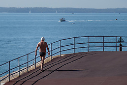 © Licensed to London News Pictures. 09/10/2015. Southsea, Hampshire, UK. A man in speedos after a dip in the sea during the warm and sunny October weather in Southsea in Hampshire. Photo credit : Rob Arnold/LNP