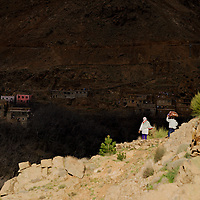 Mother and daughter returning home, through on the path by the valley.