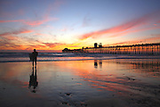 Silhouette of a Surfer on the Beach by Oceanside Pier at Sunset