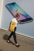 Phone user walks past Samsung shop window ad for new S6 model. Walking along the street in London's Soho, we see the women walking with her own handset checking messages or listening to music. In the background is Samsung's latest smartphone model, being launched in all media this week in an attempt to win back users from a new iPhone range. Samsung Galaxy S6 and Samsung Galaxy S6 Edge are Android smartphones manufactured and marketed by Samsung Electronics. The S6 and S6 Edge jointly serve as successors to the Galaxy S5. The smartphones were officially unveiled in a press conference at Mobile World Congress on 1 March 2015.