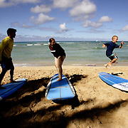 Visitors to Waikiki beach in Honolulu, Hawaii learn how to stand and switch positions during a surf school lesson before heading into the water.