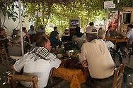 Turkish and Syrian Kurds sit in a cultural cafe to watch the latest news in Suruç close to Turkey's border with Syria and the site of tens of thousands of refugees fleeing across the border to Turkey.
