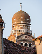 """Madonna dell'Orto church was erected by the now-defunct Humiliati religious order in the mid 1300s in the sestiere of Cannaregio, Venice, in Italy, Europe. The brickwork bell tower was finished in 1503 with an onion dome in Eastern style, topped by a white marble statue of the Redeemer. The photo is taken from a hotel room in Antica Raffineria (www.anticaraffineria.it). Venice (Venezia) is the capital of Italy's Veneto region, named for the ancient Veneti people from the 900s BC. The romantic """"City of Canals"""" stretches across 100+ small islands in the marshy Venetian Lagoon along the Adriatic Sea in northeast Italy. The Republic of Venice was a major maritime power during the Middle Ages and Renaissance, a staging area for the Crusades, and a major center of art and commerce (silk, grain and spice trade) from the 1200s to 1600s. The wealthy legacy of Venice stands today in a rich architecture combining Gothic, Byzantine, and Arab styles."""