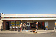 Amusement arcade with passers by in the small seaside village of Pagham in West Sussex, England, UK.