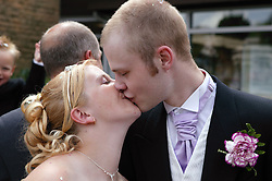Bride and groom kissing outside church,