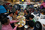 """A family celebrate """"Tet"""" (New Year) with a feast inside their shophouse business of selling prams and children's cars, Old Quarter."""