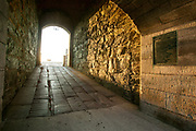 Newport, RI - Sun streams through the entrance on the worn stones of the tunnel to Fort Adams inner quad.