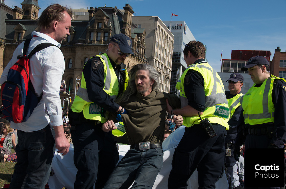 A man is helped on to a stretcher by paramedics. April 20, 2014.