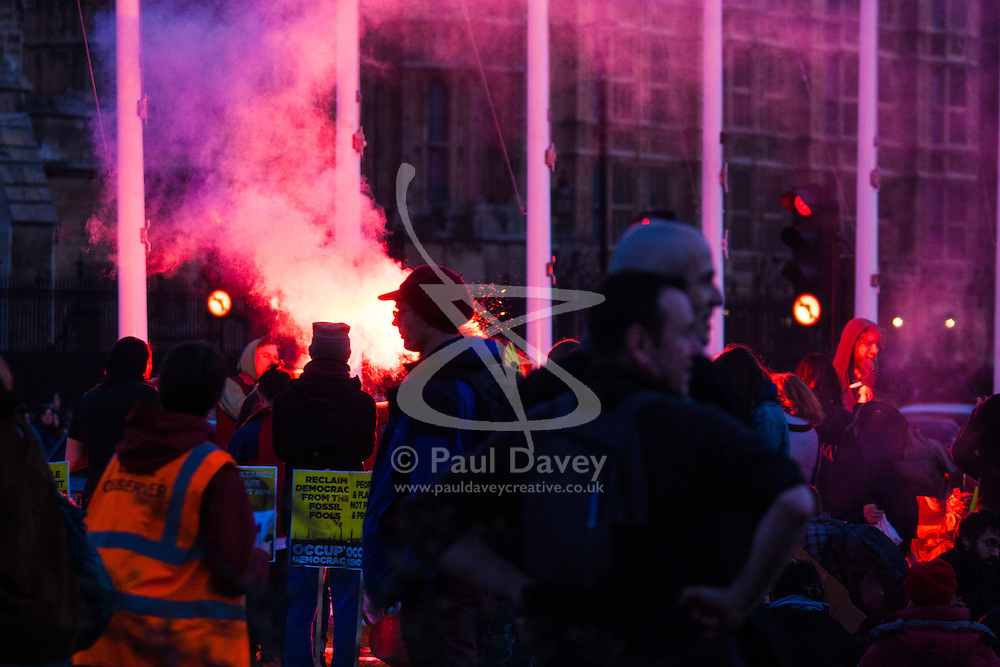 London, March 7th 2015. Following the Climate march through London, masked anarchists and environmental activists clash with police following a breakaway protest at Shell House. PICTURED: Protesters ignite a flare on Parliament Square.