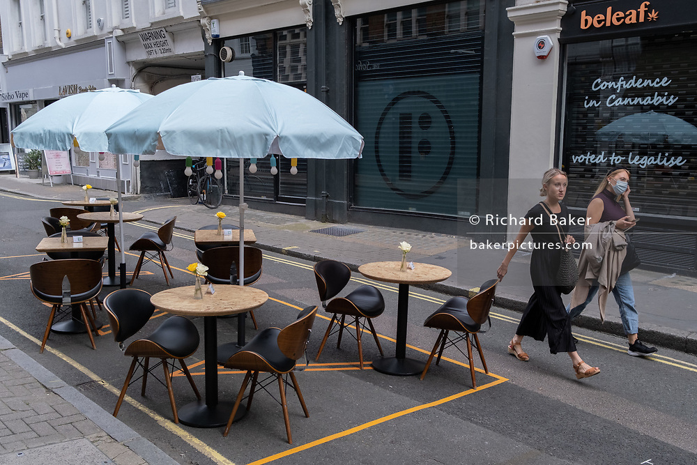 Two women walk past still empty tables and seating in Soho, days before the August Bank Holiday when the streets of this lively district of the capital are expected to be busy during the Coronavirus pandemic, on 26th August 2020, in London, England.