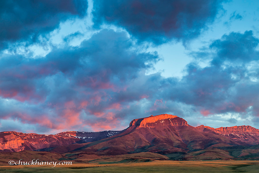 Fiery sunrise light strikes Ear Mountain along the Rocky Mountain Front near Choteau, Montana, USA