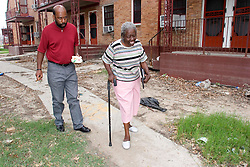 07 Oct, 2005.  New Orleans, Louisiana. Hurricane Katrina aftermath.<br /> 81 year old Rosella McKoy steps over trash washed in by the floods as she leaves her home in the deserted projects with a few precious belongings. Her nephew, Kerry Young (41yrs) gave her a ride back from Baton Rouge to check out her home in New Orleans. <br /> Photo; ©Charlie Varley/varleypix.com
