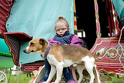© Licensed to London News Pictures. <br /> 05/06/2014. <br /> <br /> Appleby, Cumbria, England<br /> <br /> Tilly-Raine Barnes, 3, from Lancashire sits with her dog Pip on the steps of a bow top caravan as gypsies and travellers gather during the annual horse fair on 5 June, 2014 in Appleby, Cumbria. The event remains one of the largest and oldest events in Europe and gives the opportunity for travelling communities to meet friends, celebrate their music, folklore and to buy and sell horses.<br /> <br /> The event has existed under the protection of a charter granted by King James II in 1685 and it remains the most important event in the gypsy and traveller calendar.<br /> <br /> Photo credit : Ian Forsyth/LNP