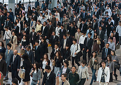 Many commuters walking through railway station during morning rush hour in central Tokyo Japan