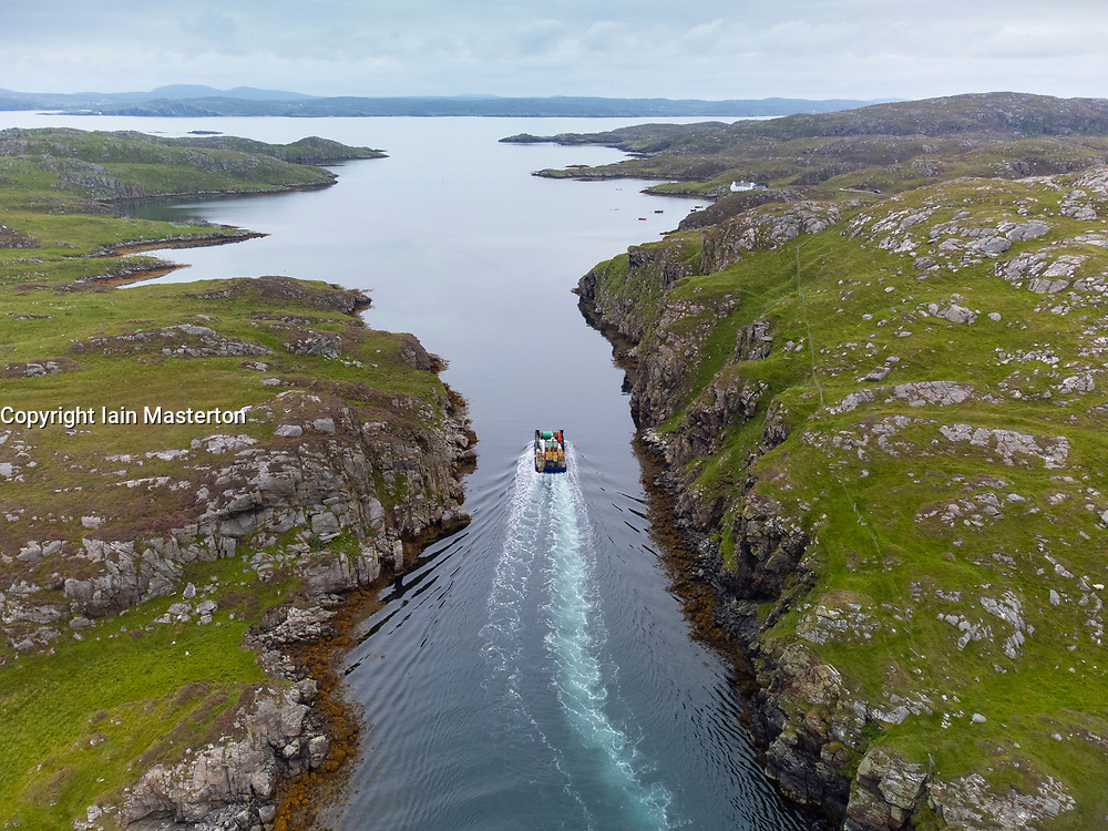 Aerial view from drone of fishing boat sailing between channel between Little Bernera and Great Bernera on  Isle of Lewis, Outer Hebrides, Scotland, UK
