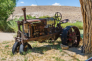 Rusting tractor in historic Benton Hot Springs, Mono County, California, USA. Benton Hot Springs (elevation 5630 feet) saw its heyday from 1862 to 1889 as a supply center for nearby mines. At the end of the 1800s, the town declined and the name Benton was transferred to nearby Benton Station.