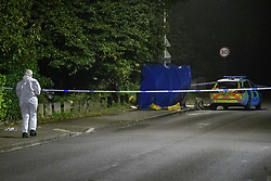 © Licensed to London News Pictures. 08/10/2021. Oxford, UK. A forensic investigator walks towards a privacy barrier alongside a Thames Valley Police car at the crime scene in Bayswater Road, Barton in Oxfordshire. Police were called just before 6:00pm today, Friday 08/10/2021, to reports of a man being stabbed, the victim, a man aged in his thirties, died of his injuries at the scene. Photo credit: Peter Manning/LNP