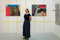 © Licensed to London News Pictures. 16/06/2021. LONDON, UK. A staff member poses with works by Ayo Akingbade at a preview of the RA Schools Show 2021, exhibiting the UK's newest artistic talent graduating from the RA Schools at the Royal Academy of Arts until 4 July 2021.  Photo credit: Stephen Chung/LNP