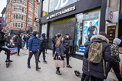 Licensed to London News Pictures. 12/04/2021. London, UK. Members of the public leave JD sports clothing shop in Oxford Street, London as police patrol the area. For the first time in months, pubs and shops across England open up and welcome customers back to their stores as the Covid-19 restrictions are lifted. Prime Minister Boris Johnson announced last week that non-essential shop, restaurants with outside seating , hairdressers and gyms can reopen today after 4 months of Covid-19 lockdowns. Photo credit: Alex Lentati/LNP