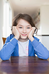 Portrait of girl sitting at wooden table, smiling