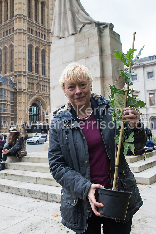 London, UK. 8 October, 2019. Anna Eagle, Labour MP for Wallasey, receives a tree from Extinction Rebellion climate activists in Old Palace Yard on the second day of International Rebellion protests. Activists created a fledgling forest of potted native trees outside Parliament as part of an initiative named Reforest Earth and they were then presented to MPs to call on the government to plant billions of trees across the UK and support the planting of trillions more around the world.