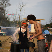 Climate Camp by Kingsnorth 2008.Camp for Climate Action is a movement made up of a lose network of people and environmental groups, wanting to stop climate change.  Through the Climate Camp they highlight issues such as aviation emission and CO2 emissions from coal power plants.  The Camp for Climate Camp wants to create a forum for people to discuss, learn and to act on climate change and to put pressure on the UK government to change its policies on polloting industries to make them commit to much more green policies. .The Climate Camp at Kingsnorth is the third camp running, previous years were by Heathrow, London and Drax coal power plant in Yorkshire. ..Boiling water for teas and coffees on the ingenious Rocket stoves, made out of old olive oil drums.