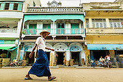 "14 JUNE 2013 -  PATHEIN, AYEYARWADY, MYANMAR: People in traditional Burmese clothing called the ""longyi"" walk down a street in Pathein. Pathein, sometimes also called Bassein, is a port city and the capital of the Ayeyarwady Region, Burma. It lies on the Pathein River (Bassein), which is a western branch of the Irrawaddy River. It's the fourth largest city in Myanmar (Burma) about 190 km west of Yangon.   PHOTO BY JACK KURTZ"