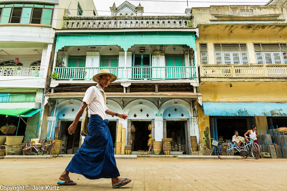 """14 JUNE 2013 -  PATHEIN, AYEYARWADY, MYANMAR: People in traditional Burmese clothing called the """"longyi"""" walk down a street in Pathein. Pathein, sometimes also called Bassein, is a port city and the capital of the Ayeyarwady Region, Burma. It lies on the Pathein River (Bassein), which is a western branch of the Irrawaddy River. It's the fourth largest city in Myanmar (Burma) about 190 km west of Yangon.   PHOTO BY JACK KURTZ"""