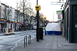 © Licensed to London News Pictures. 30/01/2019. London, UK.  A police forensic tent the crime scene in Caledonian Road in Islington, where a 17 year old man suffered stab injuries last night and pronounced dead at the scene by the London Ambulance Service. Two males were arrested near the scene and charged by police on suspicion of murder.  Photo credit: Vickie Flores/LNP