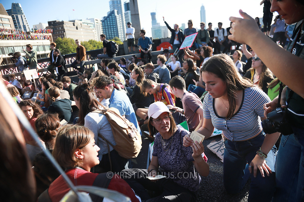 Tens of thousands took to the streets in Central London taking part in the the Global Climate Strike, September 20th 2019, London, United Kingdom.  Bust cards are handed out. For a short while Lambeth Bridge was occupied by sitting protesters, most of them teenagers. The Police quickly cleared the bridge and opened it up to traffic again. The day of strike for the climate was a global event with millions taking part across the globe. The strike was inspired by Greta Thunberg, a Swedish school girl who started the first school strike for the climate. Her action inspired school children across the world to go on strike demanding radical climate change policies to save their future. On September 20th adults aand children alike went out on strike to demand radical political change and climate justice. The day included speeches and a march through central London.