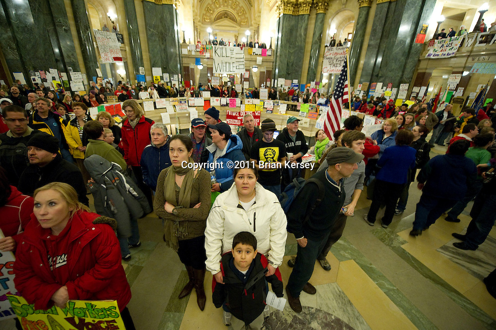 Protesters watch a live feed of a state assembly session as members vote to engross controversial legislation at the state Capitol in Madison, Wisconsin on February 24, 2011. The legislation, proposed by Republican Gov. Scott Walker, includes cuts in benefits for state workers and takes away many of their collective bargaining rights.    (Photo by Brian Kersey)