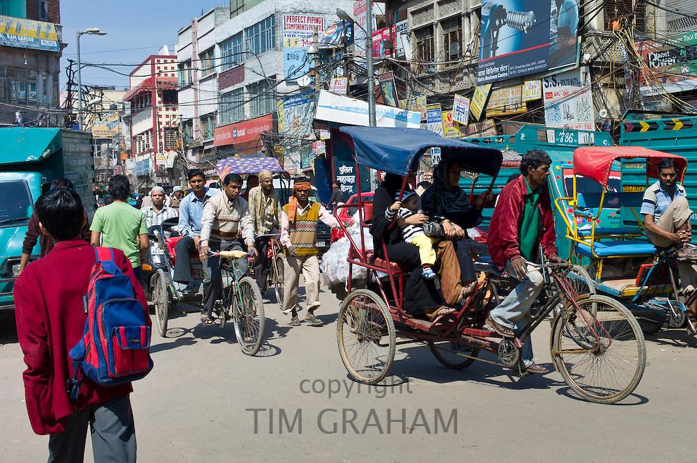 Schoolboy in school uniform heads to school along crowded street at Chawri Bazar in Old Delhi, India