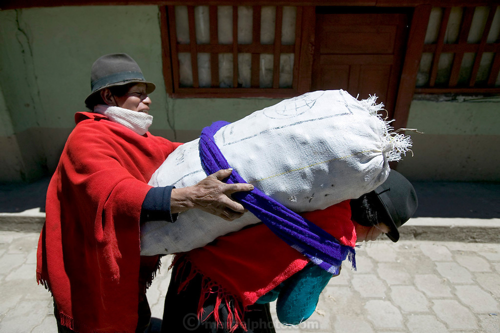 Market day  in Ecaudor is bustling as families from all over the hills stock up on food. Here a man ties a 100-lb. bag of potatoes onto his wife's back. Hungry Planet: What the World Eats (p. 110).