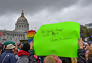 """The crowd of marchers gather at Civic Center Plaza in front of San Francisco City Hall as rain clouds loom above. A sign in the ari reads, """"We beat fear with hope,"""" a quote from Justin Trudeau."""