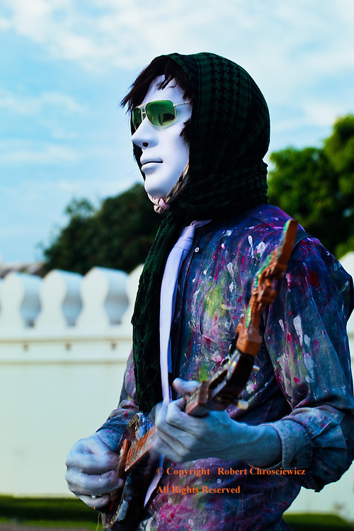 A Whiter Shade of Pale: A young man earns his next meal playing electric guitar while wearing a white mask, near the Imperial Palace, Bangkok, Thailand.