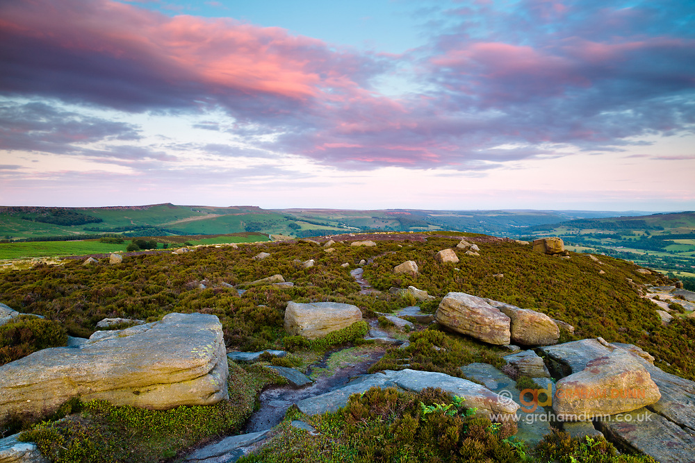 Gritstone boulders on Bamford Moor catch the last light of the day below a stunning sunset sky. A colourful landscape scene in the Derbyshire Peak District, England, UK.